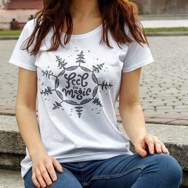 Biała damska koszulka z krótkim rękawem, t-shirt mocy z napisem: feel the magic, dookoła napisu są drzewa, ptaki i gwiazdy