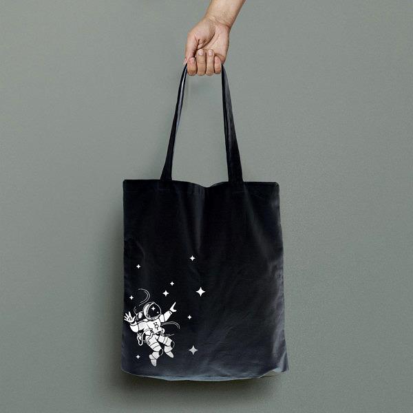 czarna torba na zakupy z 100% bawełny, na ramię. Biały nadruk z astronautą w kosmosie