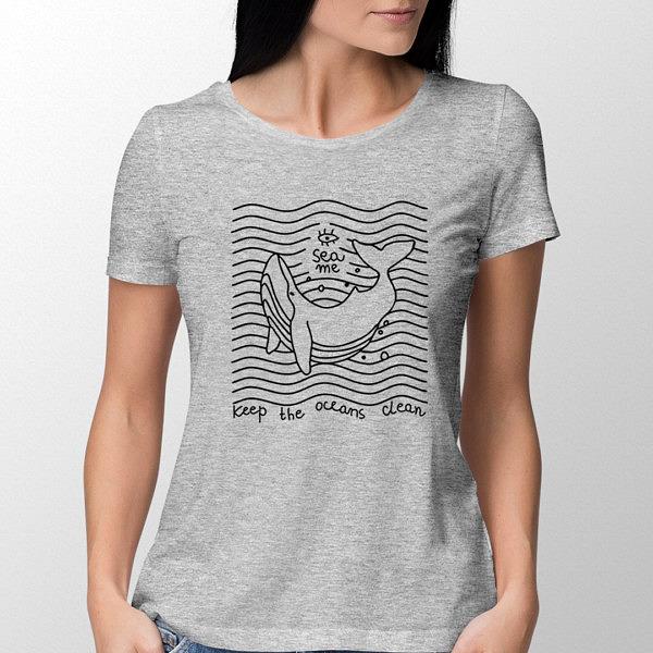 """Dziewczyna w szarej damskiej koszulkce z nadrukiem flex. Wieloryb w stylu lineart na tle równoległych do siebie fal. Nad nim napis SEA ME, pod spodem: """"Keep oceans clean""""."""
