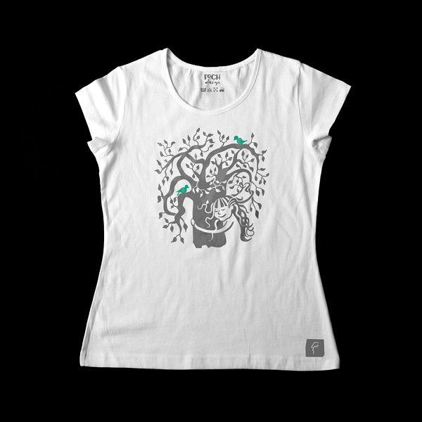 Dziewcznynka z rozwianymi włosami przytula drzewo, na drzewie siedzą ptaki, ona we włosach ma liście. Wzór na białej koszulce.