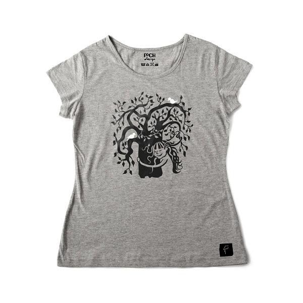 Dziewcznynka z rozwianymi włosami przytula drzewo, na drzewie siedzą ptaki, ona we włosach ma liście. Wzór na szarej koszulce.