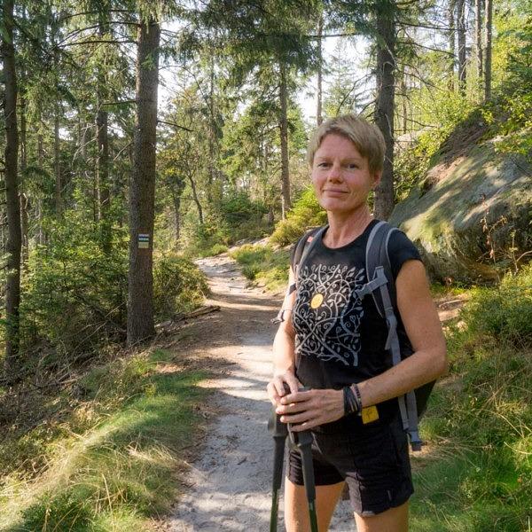 Droga przez las, kobieta, blondynka na szlaku górskim, wycieczka z kijami nordic walking, z plecakiem, ubrana na sportowo, czarny t-shirt bawełniany, z nadrukiem, ciekawy wzór, szary motyw roślinny, pośrodku żółty smiley